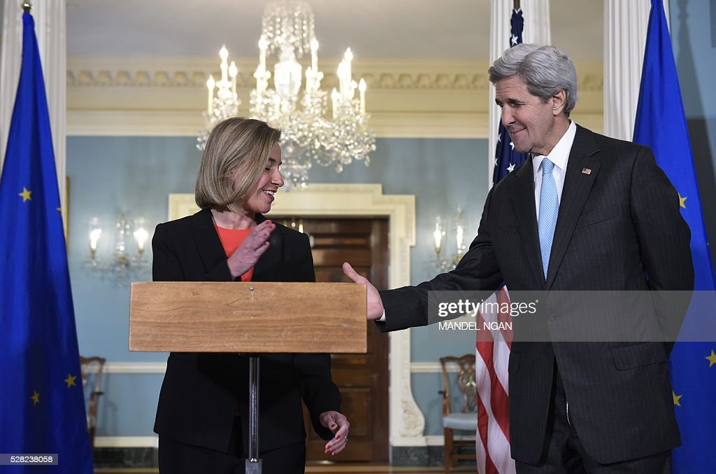 European Union Foreign Affairs and Security Policy High Representative Federica Mogherini (L) reaches out to shake hands with US Secretary of State John Kerry at the State Department on May 4, 2016. / AFP / MANDEL