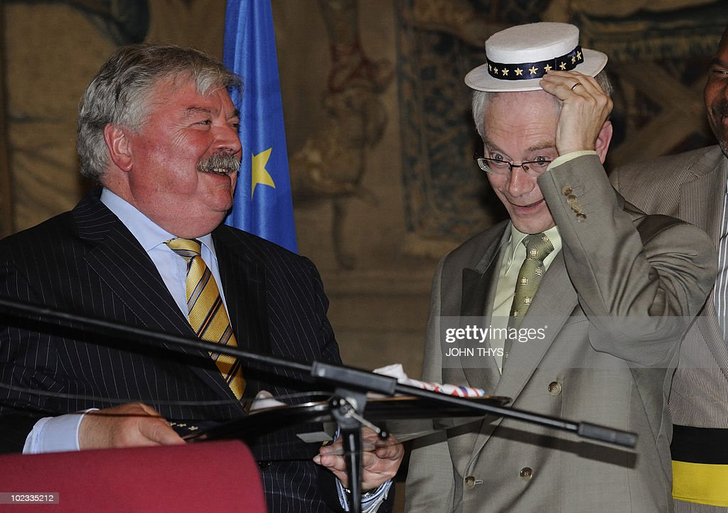 European Union President Belgian Herman Van Rompuy (R) and mayor of Brussels Freddy Tielemans (L) offer a European costume to the manneken Pis association in Brussels on June 23, 2010.