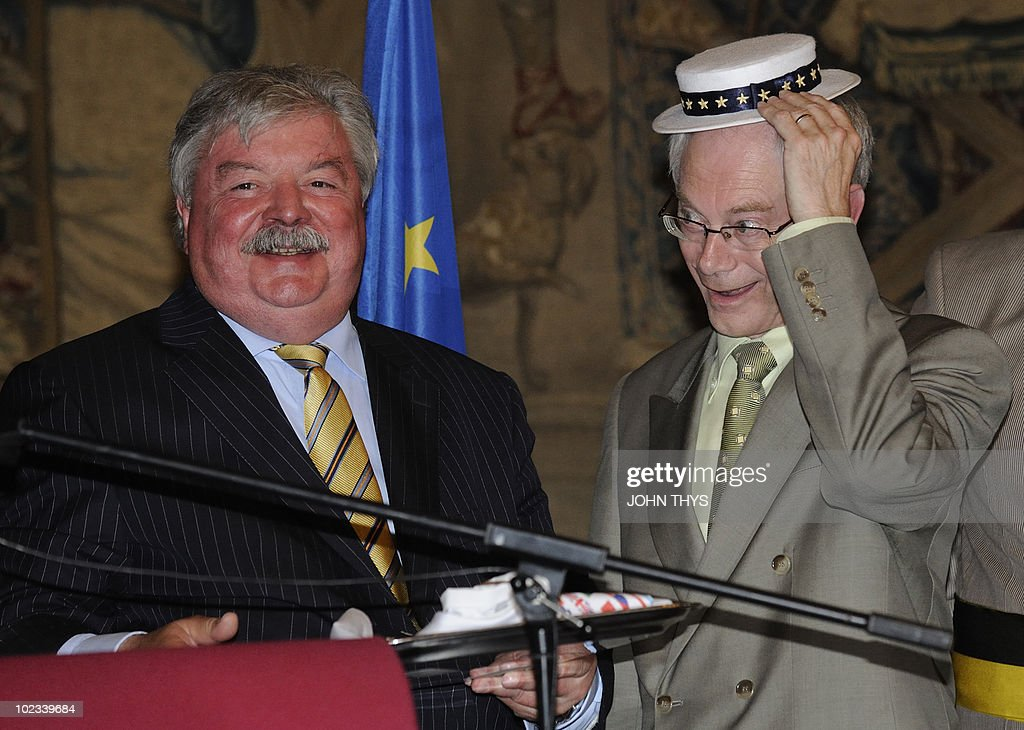 European Union President Belgian Herman Van Rompuy (R) and mayor of Brussels Freddy Tielemans (L) offer a European costume to the manneken Pis association in Brussels on June 23, 2010. AFP PHOTO JOHN THYS
