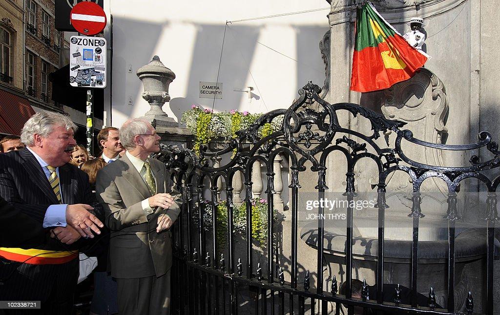European Union President Belgian Herman Van Rompuy (C) and mayor of Brussels Freddy Tielemans (L) inaugurate the manneken Pis with a European costume in Brussels on June 23, 2010.