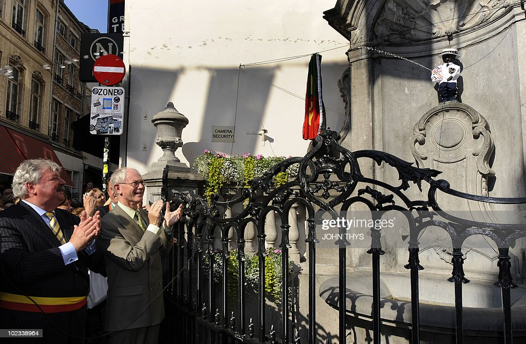 European Union President Belgian Herman Van Rompuy (C) and mayor of Brussels Freddy Tielemans (L) inaugurate the manneken Pis with a European costume in Brussels on June 23, 2010. AFP PHOTO JOHN THYS