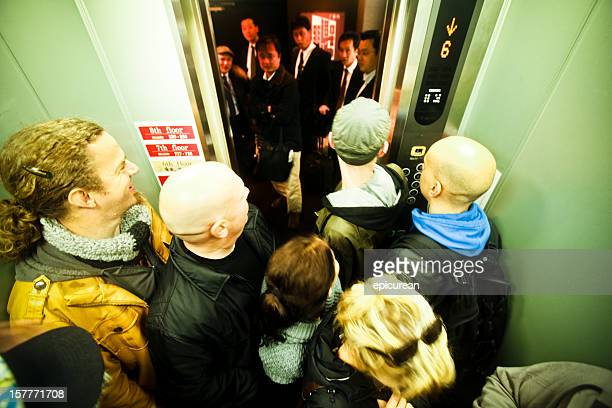 Europeans in elevator greet a waiting group of Japanese businessmen