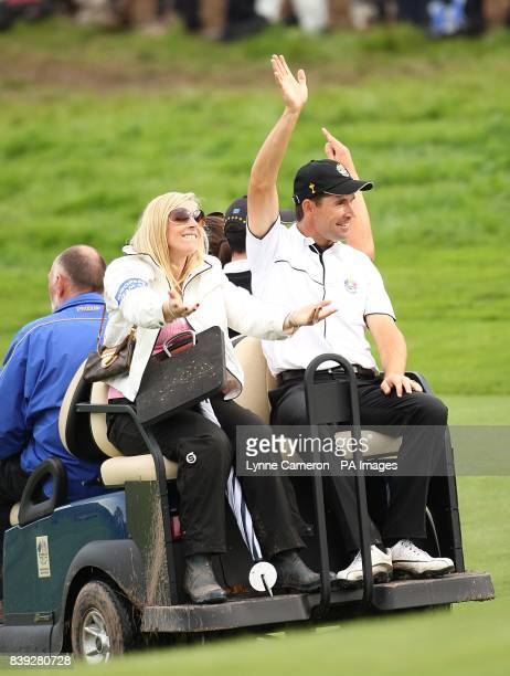 Europe's Padraig Harrington and his wife Caroline acknowledge the cheers of the crowd after he won his threesomes match with teammate Ross Fisher on...