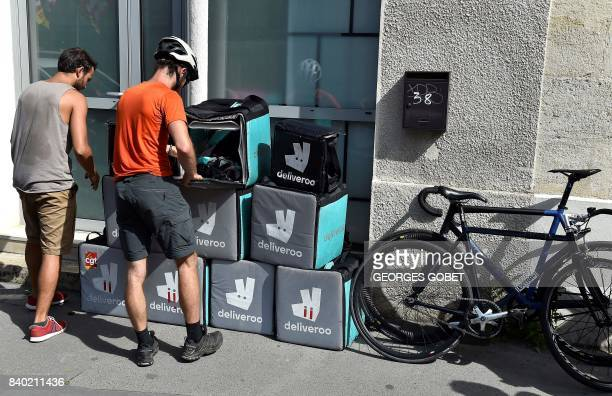 Riders working for the food delivery company Deliveroo pile up their delivery bags in front of the company's offices in Bordeaux southwestern France...