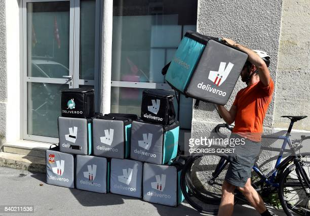 A rider working for the food delivery company Deliveroo piles up his delivery bag with others in front of the company's offices in Bordeaux...