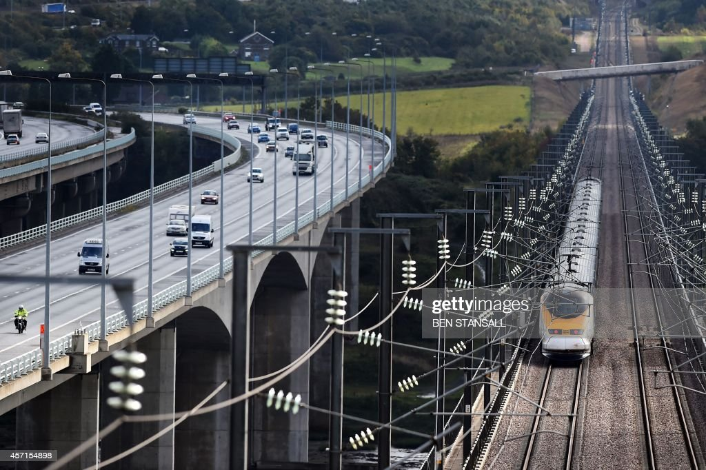 A Eurostar train is seen beside traffic on the motorway near Rochester south of London on October 13 2014 Britain's government officially launched on...