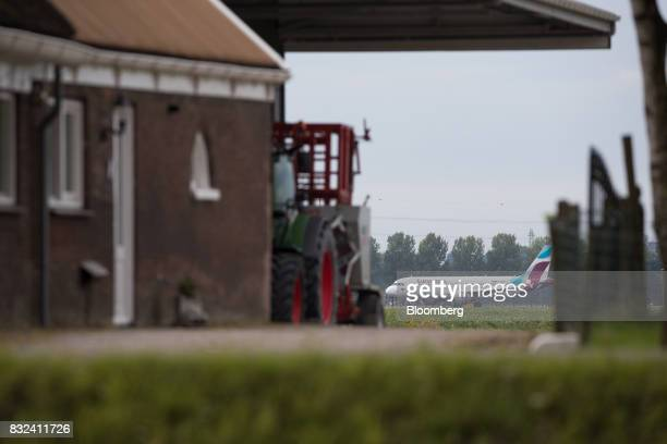 A Eurowings passenger aircraft the lowcost carrier operated by Deutsche Lufthansa AG taxis beyond a farm building after landing at Schiphol airport...