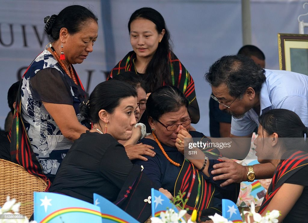 Eustar Khulu (C) wife of National Socialist Council of Nagaland-Isak Muivah (NSCN-IM) leader Isak Chishi Swu is comforted by relatives as she breaks down during during Swu's funeral service in Dimapur on June 30, 2016, in the north-east Indian state of Nagaland. Thousands of mourners attended the service to pay tribute to Isak Chishi Swu chairman of the NSCN-IM who died at a hospital in Delhi on June 28. NSCN-IM was formed in 1980 by Muivah and Swu and others with the objective of establishing a sovereign state for Naga tribes in north-east India and northern Burma. The Indian government signed a 'peace treaty with the NSCN-IM in April 2015. / AFP / STR
