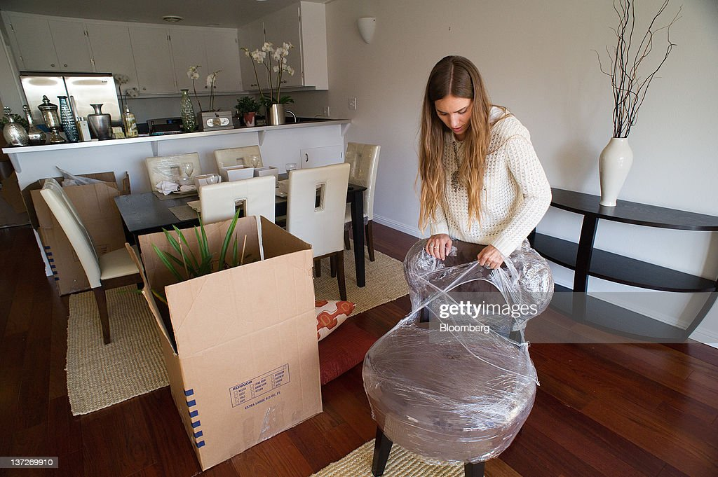 Eva Holbrook, a home stager for Bella Casa Home Staging, removes protective  wrapping from