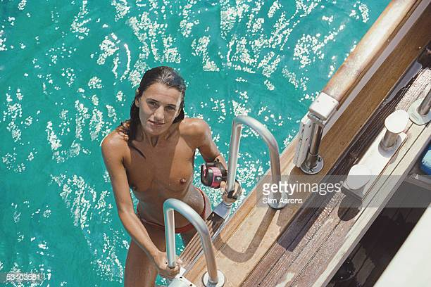 Eva Maria Lopez takes a dip in the sea from the deck of Serena her boyfriend's luxury yacht off Formentera in the Balearic Islands August 1989