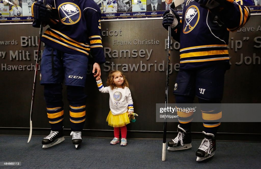 Eva Scott, 2, holds hands with her father, John Scott of the Buffalo Sabres, before the third period of their game against the New York Islanders on April 13, 2014 at the First Niagara Center in Buffalo, New York.