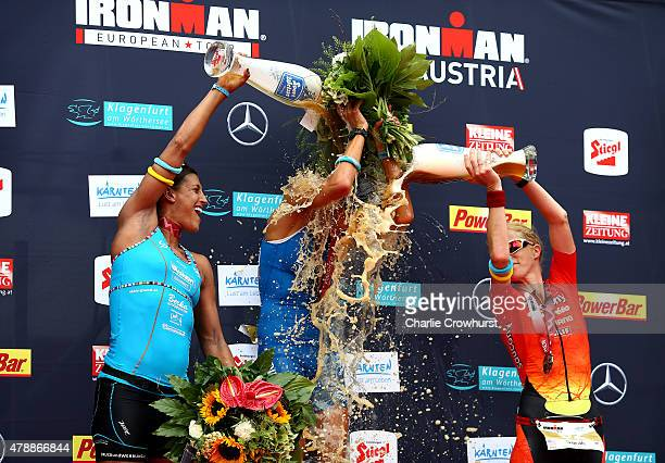 Eva Wutti of Austria is drowned in beer by Lise Hutthaler of Austria and Sarah Piampiano of America as she wins the womens race during Ironman...