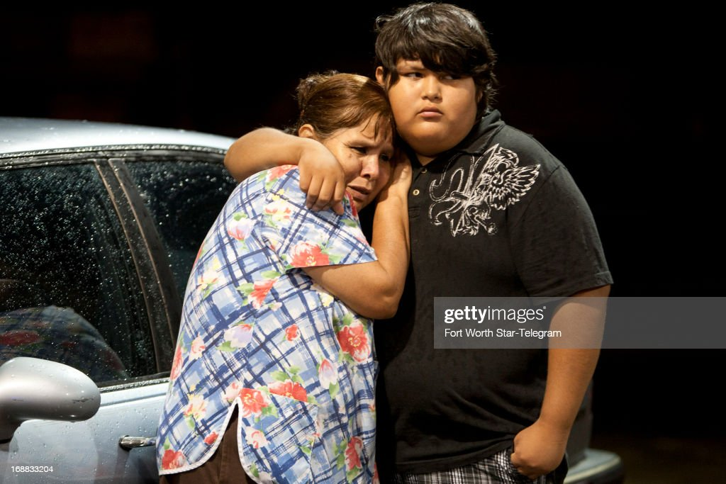 Eva Zapata, left, waits with family member Dario Segura for news of her children, who live in the Granbury, Texas, neighborhood of Rancho Brazos that was evacuated after storms on Wednesday, May 15, 2013.