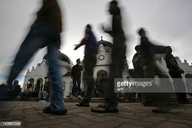 Evacuated Acehnese residents walk in front of the historic Baiturrahman grand mosque in the capital Banda Aceh after a powerful earthquake hit the...