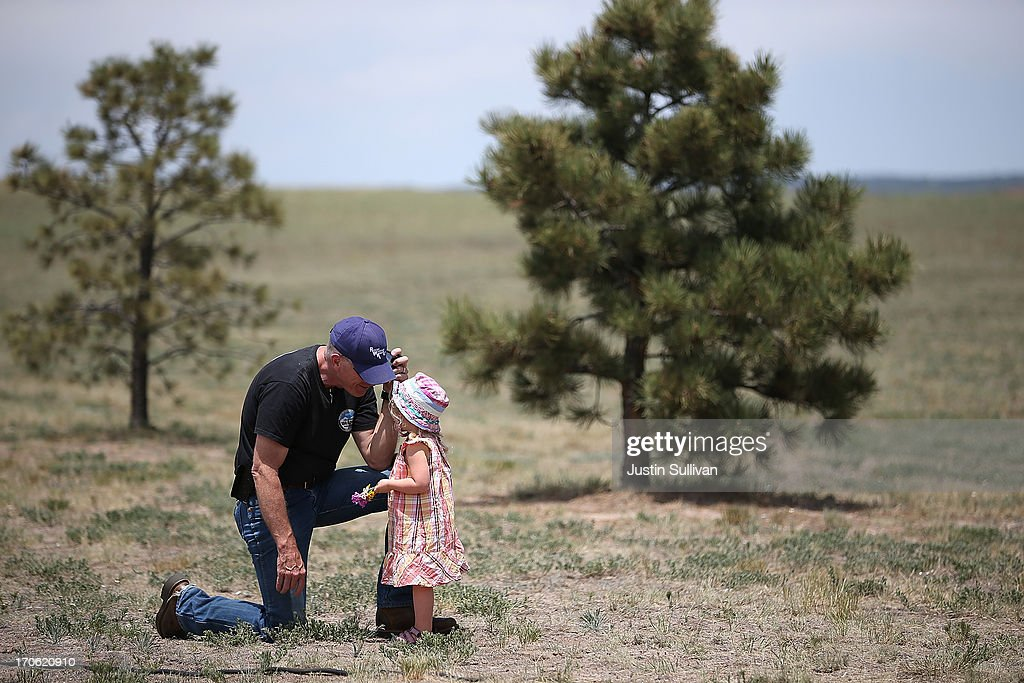 Evacuated resident Kerry Abernathy plays with his granddaughter Saylor Jean Brown during a press conference about the Black Forest fire on June 15, 2013 in Colorado Springs, Colorado. The Black Forest fire is the most destructive in Colorado history, having consumed more than 15,000 acres as of this morning while destroying 473 homes. The fire is 45 percent contained. Two people have died in the fire.