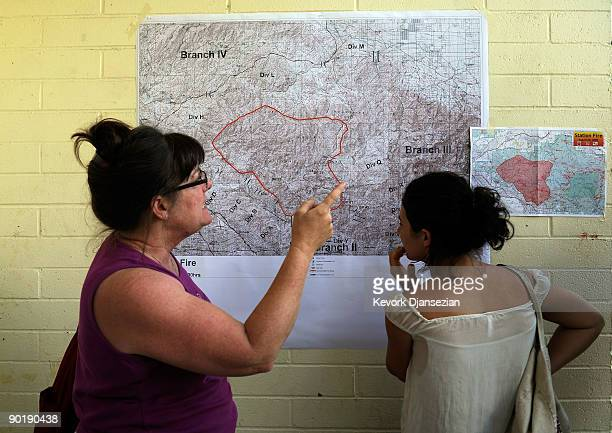 Evacuated resident of Altadena California Cecilia Miller and Teresa Martinez look at a map of the Station Fire posted on a wall at an evacuation...