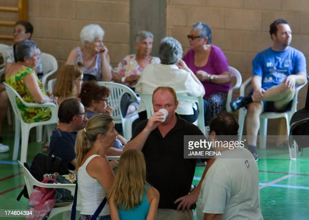 Evacuated residents of Estellencs react at a sports hall of Esporles on the island of Mallorca following a massive forest fire in the area of Andratx...