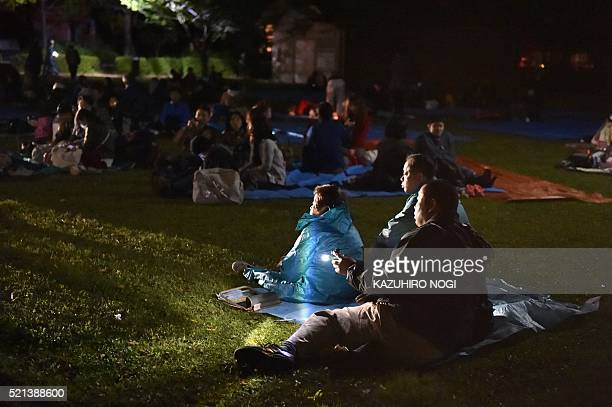 TOPSHOT Evacuated residents wait at a park in Higashiku in Kumamoto City on April 16 2016 A strong 70 earthquake hit southern Japan early the US...