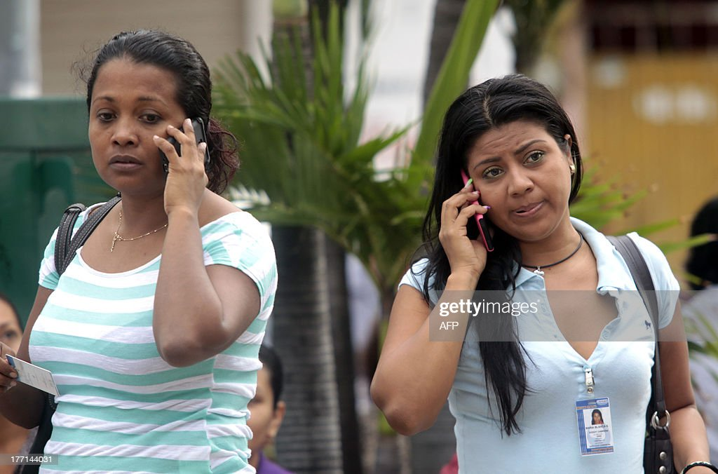 Evacuated women speak on their mobile phones in Acapulco after a 5.62-magnitude aftershock which was reported minutes after a 6.0 magnitude earthquake shook Mexico City on August 21, 2013. A strong 6.0 magnitude earthquake and an aftershock rattled Mexico on Wednesday, causing evacuations of buildings in the capital and hotels in the Pacific resort of Acapulco. The quake's epicenter has been located 17 km west of the town of San Marcos in the southern state of Guerrero, the National Seismology Center said. A 5.62-magnitude aftershock was reported 20 minutes later 14 km northeast of Acapulco, where rocks from a hill rolled into a street and some hotel facades showed cracks while tourists poured into the streets. AFP PHOTO / Pedro PARDO