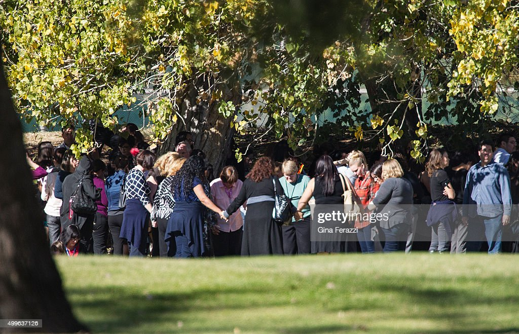 Evacuated workers pray in a circle on the San Bernardino Golf Course across the street where a mass shooting occurred at the Inland Regional Center...