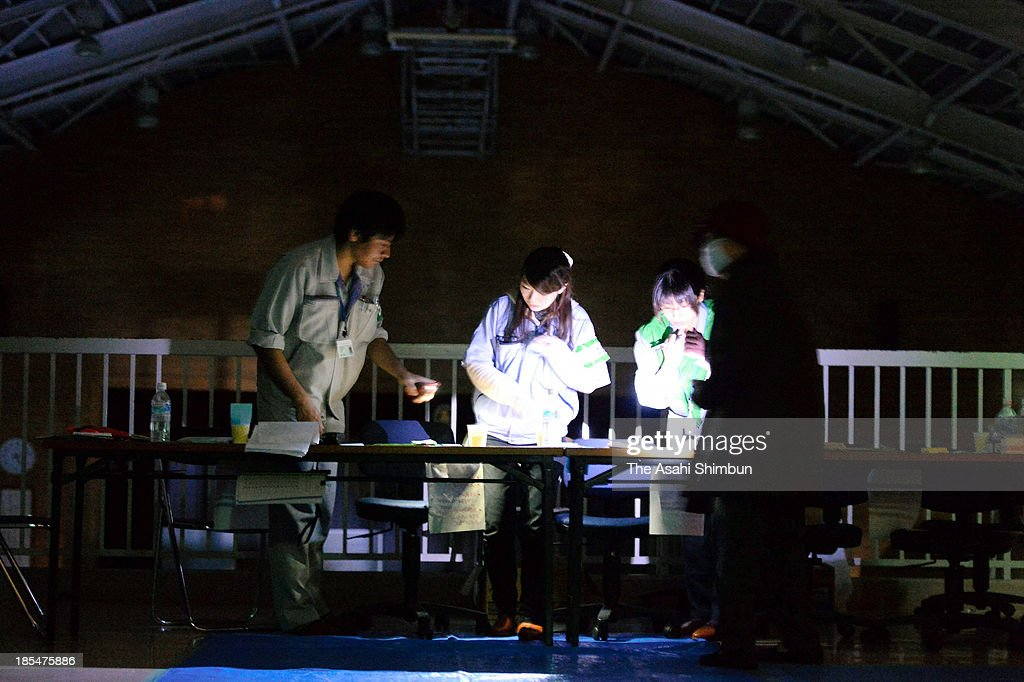 Evacuation center staffs work under the light of electric torch as the area suffering power outage at Oshima High School on October 20, 2013 in Oshima, Tokyo, Japan. The evacuation advisory was issued October 19 as another heavy rain was expected at a landslide devastated Oshima Island. The early morning downpours from Typhoon Wipha, or No. 26 on October 16 caused landslides that covered 1.14 million square meters and damaged or destroyed 283 homes, according to estimates by Oshima town officials.