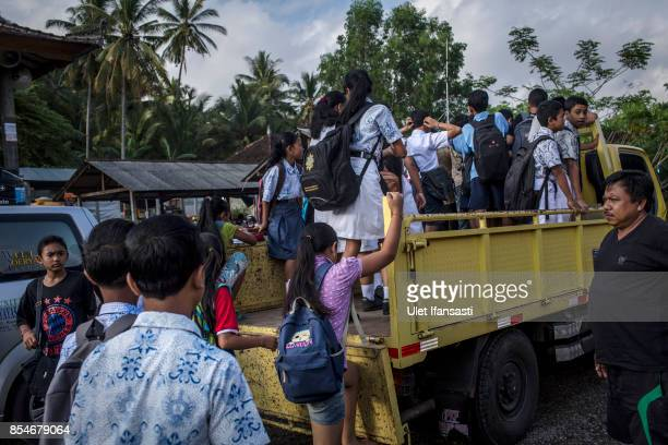 KARANGASEM BALI INDONESIA SEPTEMBER 27 Evacuee children get onto on a truck as they head off to a temporary school on September 27 2017 in Karangasem...