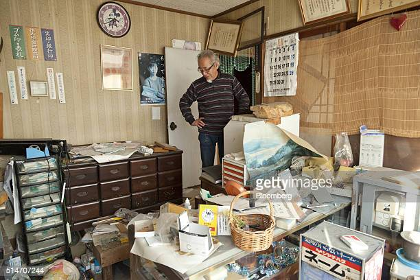 Evacuee Haruhisa Endo looks inside his home in an evacuation zone area damaged by the 2011 earthquake and tsunami in Tomioka Fukushima Prefecture...