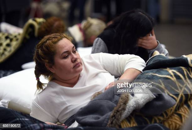 Evacuee Karina Garcia looks on at the Placer County Fairgrounds evacuation center in Roseville California on February 13 2017 Almost 200000 people...