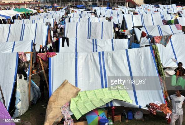 Evacuees affected by the standoff between government forces and Muslim rebels rest at their makeshift shelters at an evacuation center inside a...
