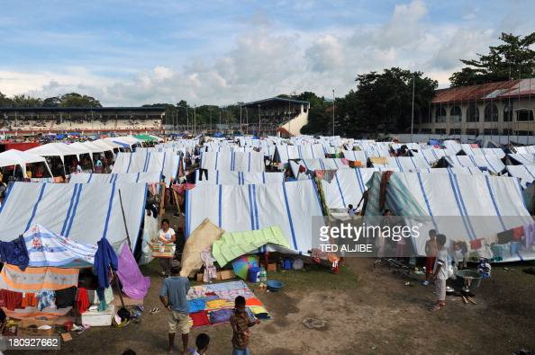 Evacuees affected by the standoff between government forces and Muslim rebels dry clothes and rest at their makeshift shelters at an evacuation...