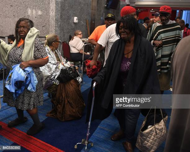 Evacuees arrive at the Convention Center shelter after evacuating from their homes when Hurricane Harvey caused heavy flooding in Houston Texas on...