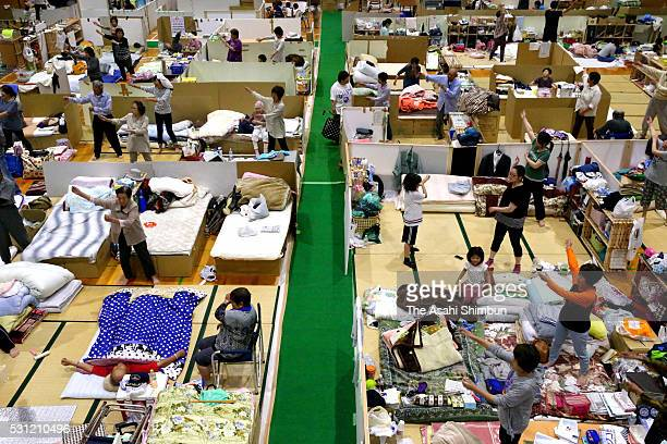 Evacuees exercise to avoid economy class syndrome at the cardboard separated gymnasium of Yamanishi Elementary School on May 13 2016 in Nishihara...