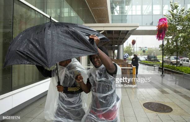 Evacuees fight the rain outside the George Brown Convention Center which has been turned into a shelter run by the American Red Cross to house...