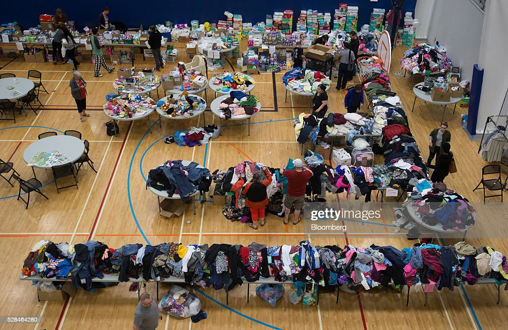 Evacuees from wildfires in the Fort McMurray area browse through clothing donations at a community center in Lac La Biche, Alberta, Canada, on Thursday, May 5, 2016. A fire fueled by shifting winds that forced more than 80,000 people to flee their homes and threatened the business district of oil-sands hub Fort McMurray, Canada, raged out of control Wednesday after consuming 80 square kilometers (30 square miles) of land and damaging 1,600 buildings. Photographer: Darryl Dyck/Bloomberg via Getty Images