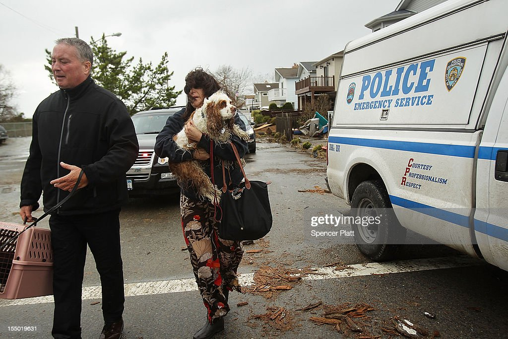 Evacuees leave after Hurricane Sandy caused major destruction after Hurricane Sandy on October 30, 2012 in the Breezy Point Neighborhood of the Queens borough of New York City. At least 40 people were reportedly killed in the U.S. by Sandy as millions of people in the eastern United States have awoken to widespread power outages, flooded homes and downed trees. New York City was hit especially hard with wide spread power outages and significant flooding in parts of the city.