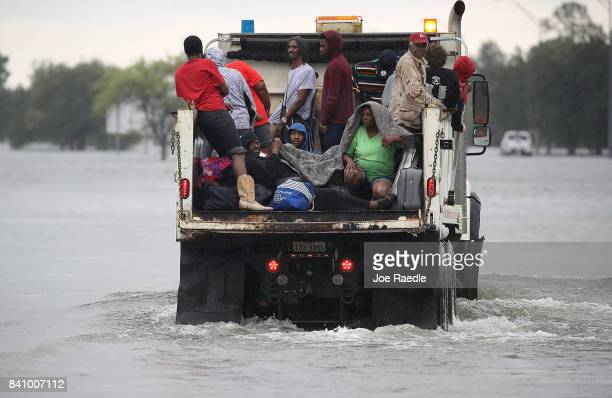 Evacuees ride on a truck after they were driven from their homes by the flooding from Hurricane Harvey on August 30 2017 in Port Arthur Texas Harvey...