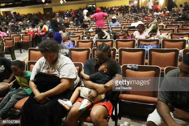 Evacuees sit in the auditorium of the Woodrow Wilson Middle School after they were evacuated from the flooding of Hurricane Harvey on August 30 2017...