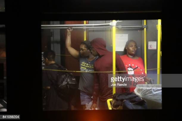 Evacuees sit on an evacuation bus as they leave Woodrow Wilson Middle School to a shelter after they were evacuated from the flooding of Hurricane...