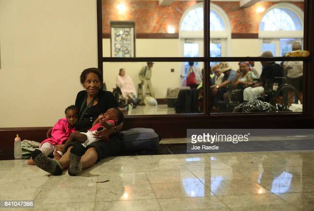Evacuees sit the hallway of the Woodrow Wilson Middle School after they were evacuated from the flooding of Hurricane Harvey on August 30 2017 in...