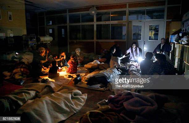 Evacuees spend time with flashlights due to power outage at an evacuation center set at Hiroyasu Elementary School on April 16 2016 in Mashiki...
