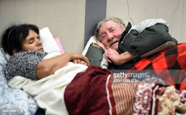 Evacuees Steve Allen and Alicia Castro lay on a cot at the Placer County Fairgrounds evacuation center in Roseville California on February 13 2017...