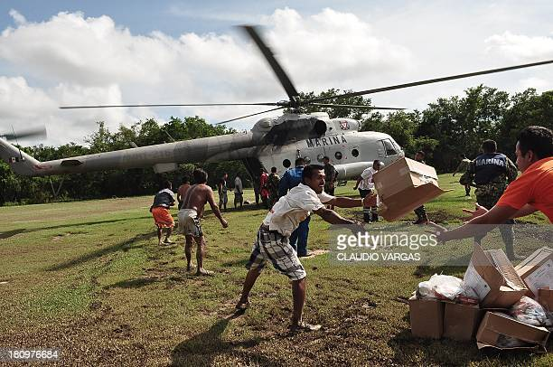 Evacuees unload food boxes from a Mexican Navy helicopter in an area of Acapulco state of Guerrero Mexico on September 18 2013 as heavy rains hit the...