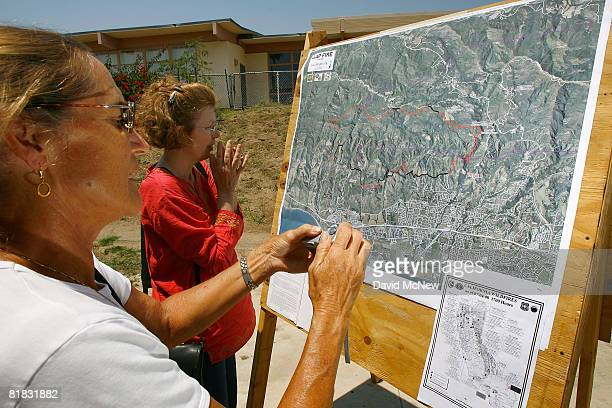 Evacuees view and photograph a fire map at an evacuation center during the Gap fire now officially the top priority fire in the state as hundreds of...