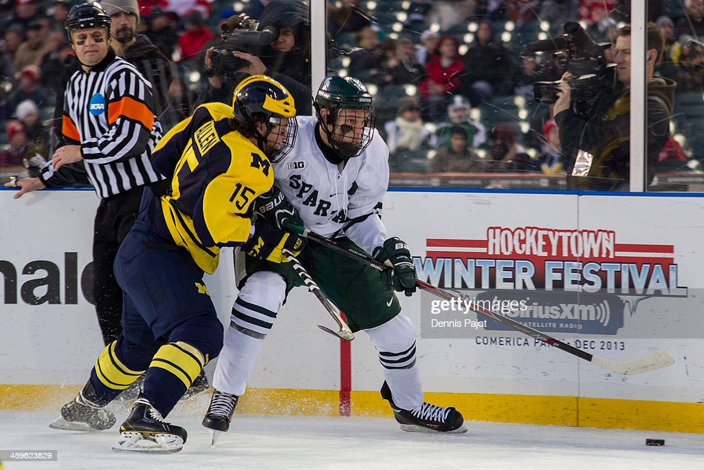 Evan Allen #15 of the Michigan Wolverines battles against Connor Wood #9 of the Michigan State Spartans on December 28, 2013 at Comerica Park in Detroit, Michigan.