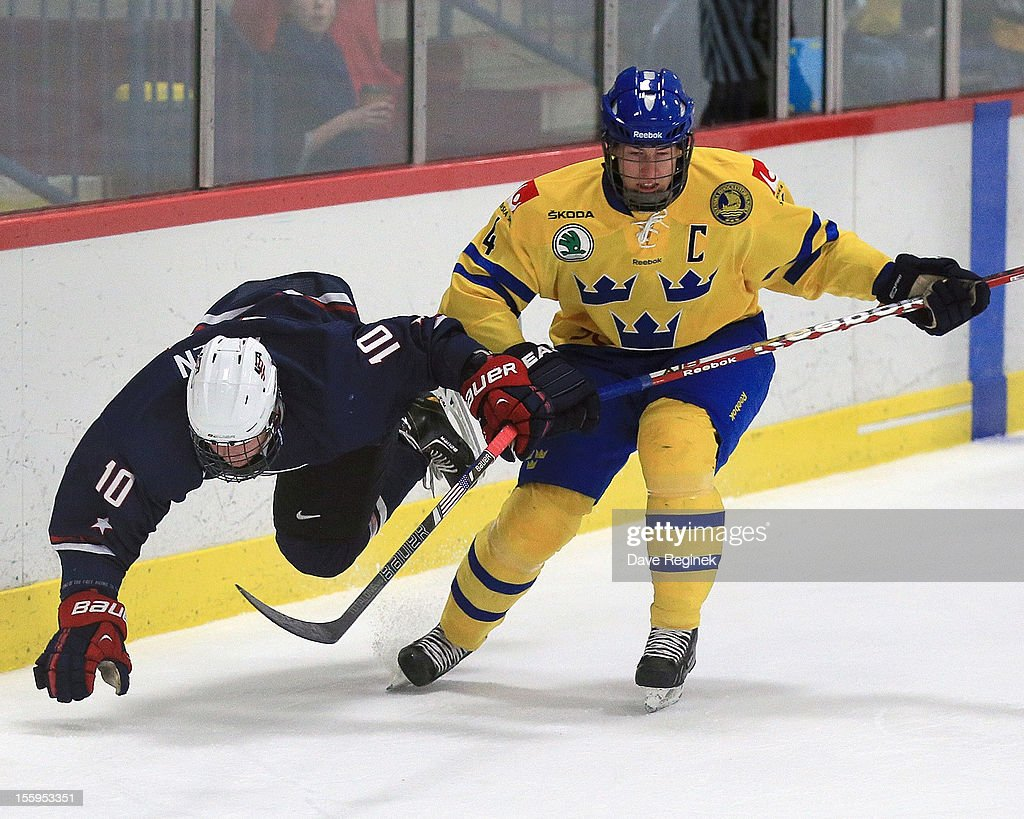 Evan Allen #10 of the USA is tripped up by Robert Hagg #4 of Sweden during the U-18 Four Nations Cup tournament on November 9, 2012 at the Ann Arbor Ice Cube in Ann Arbor, Michigan. USA won 5-3.
