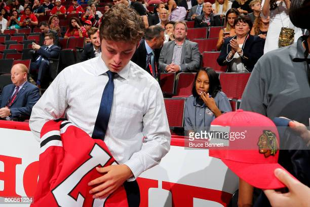 Evan Barratt puts on the Chicago Blackhawks jersey after being selected 90th overall during the 2017 NHL Draft at the United Center on June 24 2017...