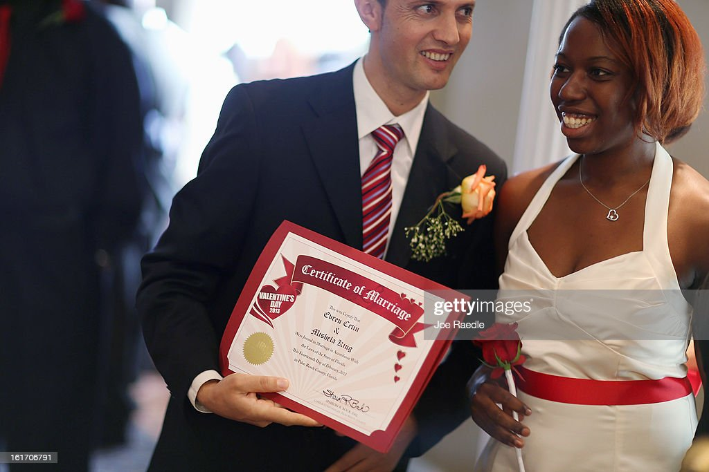 Evan Cetin and Michelle Renne (L-R) hold their marriage certificate after being wed during a group Valentine's day wedding at the National Croquet Center on February 14, 2013 in West Palm Beach, Florida. The group wedding ceremony is put on by the Palm Beach Country Clerk & Comptroller's office and approximately 40 couples tied the knot.