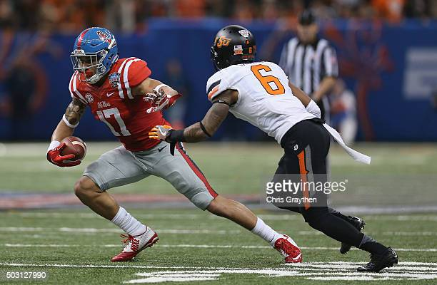 Evan Engram of the Mississippi Rebels carries the ball against Ashton Lampkin of the Oklahoma State Cowboys during the third quarter of the Allstate...
