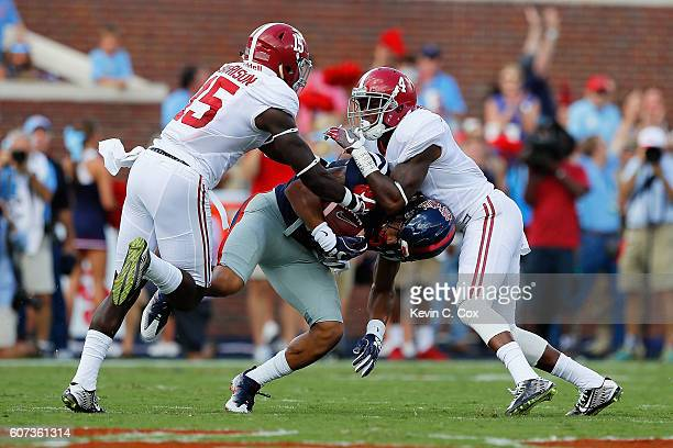 Evan Engram of the Mississippi Rebels is tackled by Eddie Jackson and Ronnie Harrison of the Alabama Crimson Tide at VaughtHemingway Stadium on...
