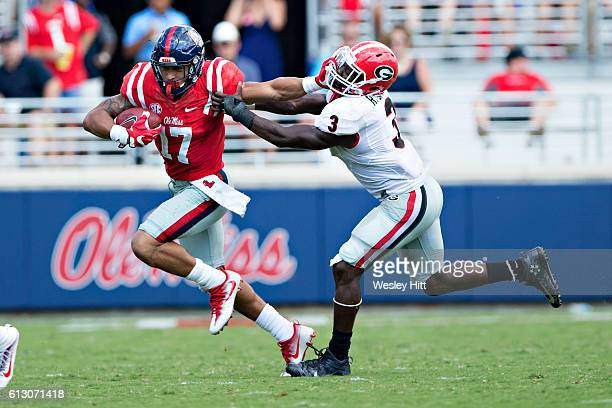 Evan Engram of the Mississippi Rebels runs the ball and stiff arms Roquan Smith of the Georgia Bulldogs at VaughtHemingway Stadium on September 24...